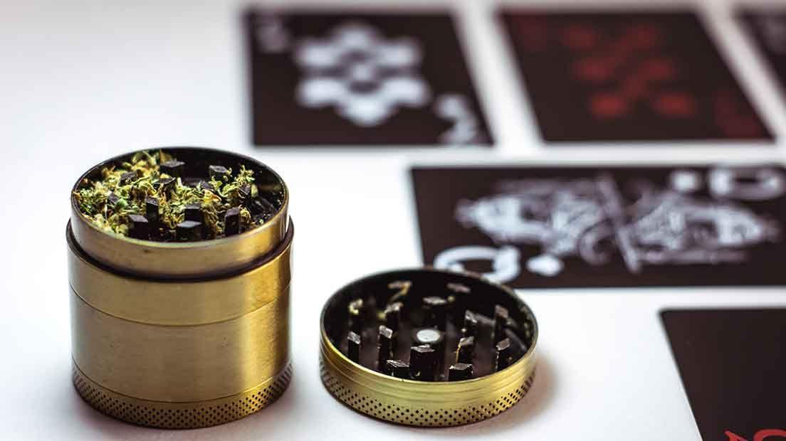 Triturar marihuana sin grinder es posible con tijeras y un vaso de chupito.